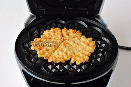 На середину вафельницы выкладывать полную столовую ложку теста и выпекать вафли до готовности.