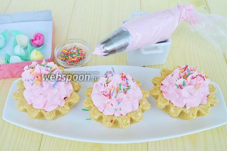 Заполнить кондитерский конверт кремом и украсить пирожные. Готовые пирожные посыпать кондитерской посыпкой.