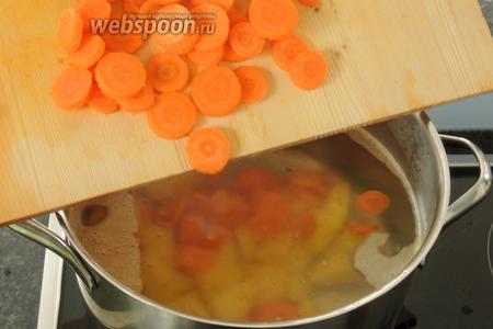 В кипящую воду опускаем нарезанные картофель и морковь. Доведём до кипения и уменьшим огонь.