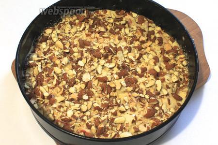 Форму слегка смазать сливочным маслом, вылить 1/3 теста. На тесто выложить дольки яблок, цедру и орехи. Залить оставшимся тестом.