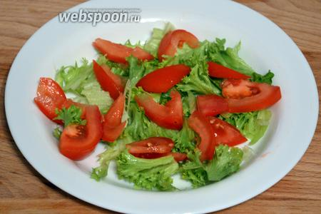 На листья салата укладываем порезанные дольками помидоры.