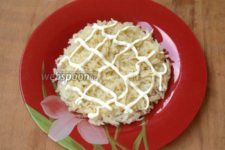 Готовый картофель остудить, очистить и натереть на тёрке. Выложить на блюдо первым слоем. Нанести сеточку из майонеза.
