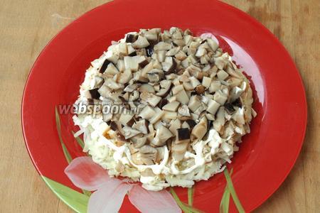 Мелко нарезать маринованные грибы и выложить их сверху курицы.