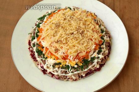 Следующий слой выложить частью твёрдого сыра, посыпать измельчёнными орешками.