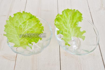 На дно креманок выложить листья салата.