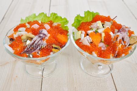 Майонез закрыть салатной смесью, заполнив креманку. Салат укрыть красной икрой, декорировать сердечками и щупальцами. Королевский салат с морепродуктами готов!
