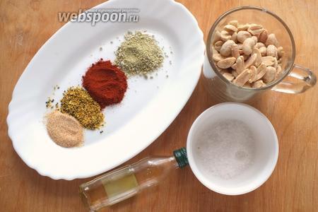 Подготовьте необходимые ингредиенты: сырой очищенный арахис, лимонный перец, кайенский перец, зелёный сыр, сушёный чеснок, соль, сахар и оливковое масло.