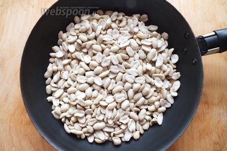 Выложите арахис на разогретую сковороду и постоянно, перемешивая, обжаривайте его на среднем огне примерно 5 минут. Разогрейте духовку до 200ºC.