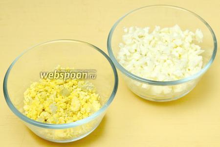 Вареные яйца разделяем на белки и желтки. Белки трём на тёрке, желтки крошим.