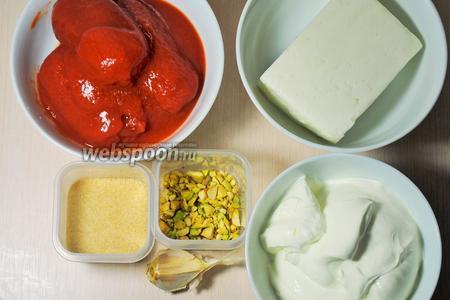 Для приготовления закуски понадобятся томаты в собственном соку, брынза, сметана, рубленые фисташки, желатин, чеснок (по желанию) и специи.