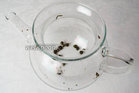 Заварочный чайник ополоснуть кипятком и засыпать лепестки зелёного чая (листья чая скручены в гранулы, при заваривании, листья раскрываются).