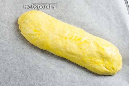 Тесто обмять. Выложить на пергаментную бумагу. Сформировать продолговатый батон. Смазать батон яичной смесью. Поставить в тепло на расстойку на 1 час 30 минут. Когда подсохнет, снова накрыть полотенцем.