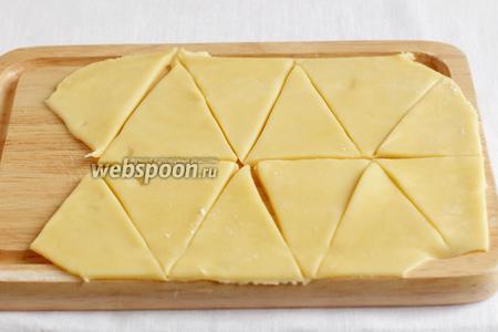 Разделить тесто на несколько частей, чтобы удобнее было с ним работать. Раскатать в пласт примерно 3 мм и нарезать на треугольнички.