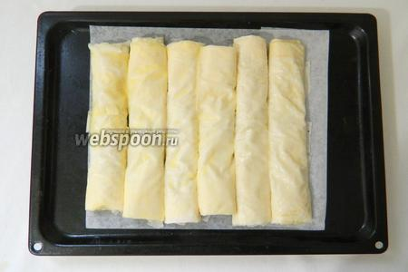 Рулеты из теста с начинкой выкладываем на противень и обмазываем сливочным маслом.