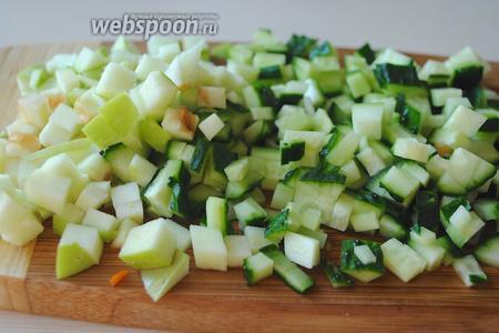 Нарежьте небольшими кубиками огурцы и полвинку яблока.