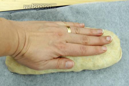 Перекладываем хлеб на застланный пекарской бумагой противень, швом вниз. Руками придавливаем и формируем овал.