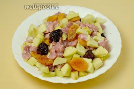 Добавляем к свинине нарезанные кубиками яблоки, курагу и чернослив, поливаем ромом и перемешиваем.