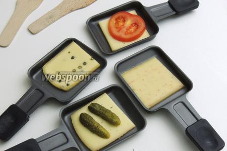 На сковородочки кладём по куску сыра. По желанию на сыр можно класть маринованные овощи.
