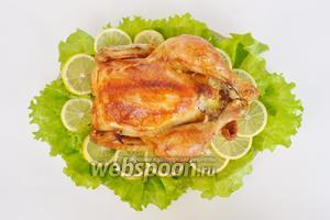 Переложить курицу на блюдо украшенное листьями салата и лимоном и подавать.