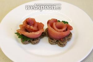 Следующую порцию хлеба смазать сливочным маслом и украсить розочкой копчёной рыбы.