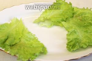 На блюдо укладываем листья салата и размещаем канапе.