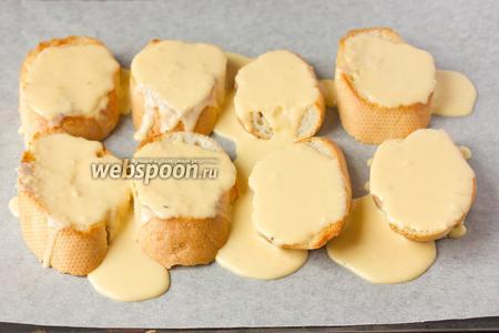 На противень, выстеленный пергаментом для выпечки, выкладываем гренки, поливаем их сырной смесью.