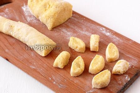 Разделить тесто на две части. Раскатать каждую часть в колбаску диаметром 2 см и нарезать кусочками толщиной 1 см.
