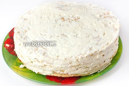 Достаём через час торт из холодильника, снимаем бортик и перекладываем его на широкое плоское блюдо, бока промазываем оставшимся кремом.