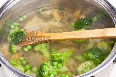 Закипятить воду в кастрюле, добавить чайную ложку соли и высыпать макароны. Варить по инструкции и за 4 минуты до готовности добавить брокколи и горошек. Через 4 минуты овощи и макароны отбросить на дуршлаг.
