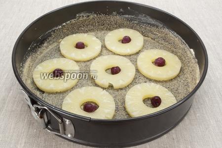 Выкладываем равномерно кружочки ананаса, внутрь каждого кладём по вишенке.