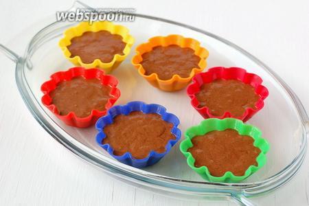 Выложить тесто в смазанные формочки для кексов.