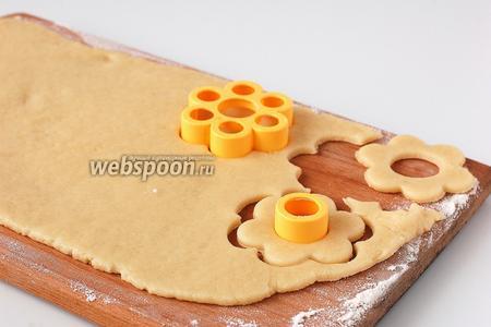 На подпыленной мукой доске раскатать тесто толщиной 3 мм. Формочкой вырезать печенье.