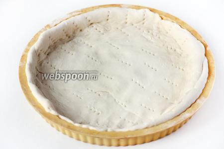Теперь подготовим основу для пирога. Для этого размороженное готовое слоёное дрожжевое тесто слегка раскатываем и выкладываем ровным слоем в форму для выпечки, формируя бортики. Делаем на тесте частые проколы вилкой.