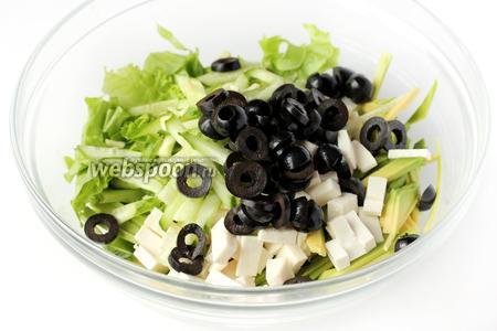К листьям салата добавляем остальные подготовленные ингредиенты: брынзу, авокадо, огурец и маслины.