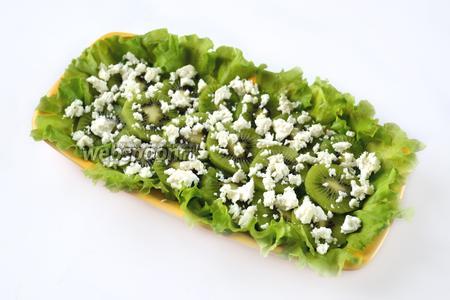 Мягкий козий сыр свободно крошим по поверхности киви.