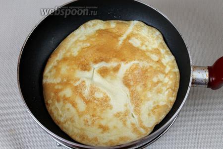 На антипригарной сковороде под крышкой выпечь из яиц блин, когда одна сторона подрумянится, можно перевернуть. Получившийся омлетный блин остудить.