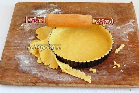 Распределить тесто по форме и пройтись сверху скалкой, обрезая лишнее тесто.