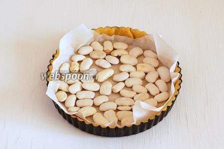 Накрыть тесто сверху бумагой для выпечки и разложить фасоль или горох. Выпекать 15 минут при 180°С.
