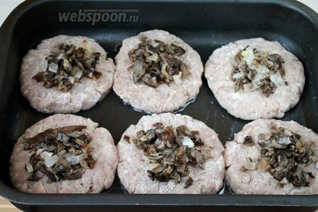 На середину каждого бифштекса положить по столовой ложке обжаренных с луком грибов.
