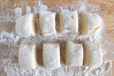 Раскатайте тесто на присыпанной мукой доске на жгуты, а заем нарежьте кусочками размером чуть больше грецкого ореха.