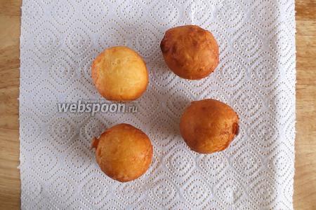 Выложите готовые пончики на бумажное полотенце для впитывания лишнего жира.