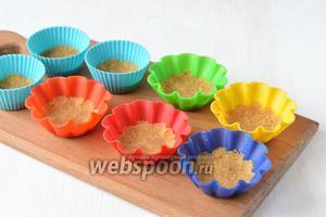 В силиконовые формочки для кексов выложить по 1 полной столовой ложке крекерной массы и хорошо прижать её ко дну формочек.
