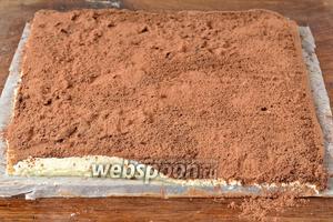 Присыпать сверху выпечку какао (2 ст. л.) и начать сворачивать сырник рулетом, помогая себе бумагой, на которой выпекался сырник. Бумага будет отходить от сырной массы хорошо и без проблем.