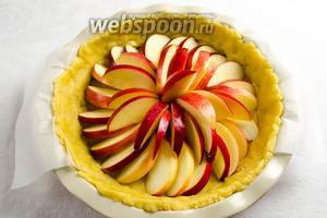 Разложить дольки яблок по кругу на дно формы. Поставить в горячую духовку 200 °C. Запекать в течение 20 минут.