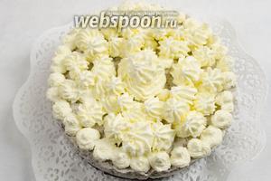 Взбить крем для украшения. Освободить торт от формы. Украсить кремом и половинками печенья. Подавать на десерт в охлаждённом виде.
