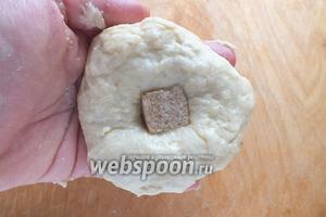 Разогрейте духовку до 200ºC. Разделите тесто на 8 частей и смазанными маслом руками сформируйте 8 булочек, вложив в каждую по кусочку сахара.