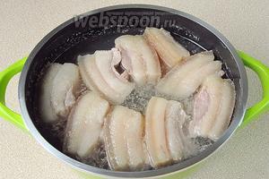 Залить брусочки сала горячим раствором соли. Жидкость должна лишь слегка покрывать его.