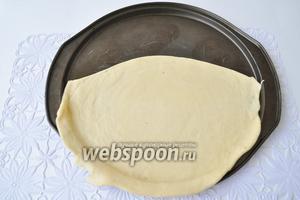 Займемся формовкой пирога. Для корзинки используем круглую форму, что позволит точнее воспроизвести корзинку. Возможно использовать форму для пиццы. Раскатаем овал и выложим в форму так, что бы он занял немного более половины круга.