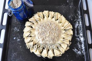 Присыпать серединку семенами подсолнечника и дать постоять 30 минут. Выпекать в духовке, разогретой до 180ºC 25-30 минут.