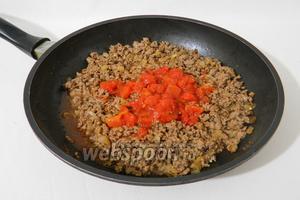 После этого добавляем консервированные томаты кусочками, подливаем 50 мл воды, накрываем крышкой и тушим до испарения жидкости.